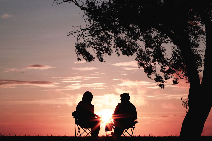 Two people talking during a sunset Photo by Harli Marten